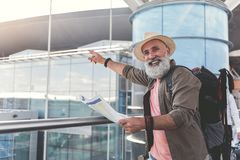 Joyous smiling elder male person having travel. Happy mature male bearded tourist is pointing somewhere and looking at camera with smile. Man holding map. Copy Stock Image