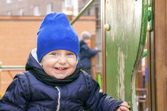 Joyous smiling kid having funny time on playground. Waist up portrait of happy child playing outside. Little boy in fashionable blue cap and jacket looking at stock images