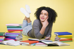 Joyous student girl reading surrounded by colorful books. Royalty Free Stock Photography