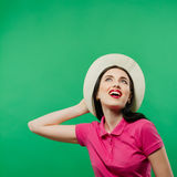 Joyous Toothy Smiling Girl with Long Hair is Posing in Cowboy Hat and Bright Pink Shirt on Green Background. royalty free stock photos
