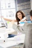 Joyous vrouwelijke voorbijgaande telefoon tot collega in bureau Royalty-vrije Stock Foto's