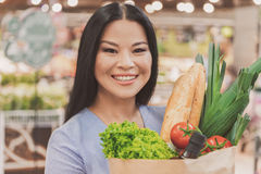 Joyous woman keeping necessary purchases stock images