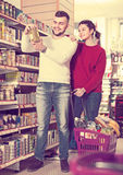 Joyous young couple choosing purchasing canned food for week at Royalty Free Stock Photos