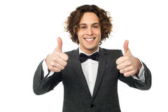 Joyous young guy gesturing double thumbs up Royalty Free Stock Photos