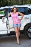 Joyous young woman in pink shirt standing near own car, full-length Stock Photos