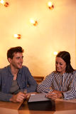 Joyously smiling young couple in restaurant Stock Photos