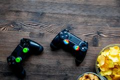 Joypad and snacks on wooden background top view space for text. Joypad for video games and snacks on wooden desk background top view space for text Stock Image