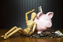 The joys of saving moneu. Manikin leaning against a piggy bank surrounded by money Stock Photos