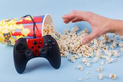 The joystick leans on a bowl with scattered popcorn and the hand wants to take it on a blue background stock photo