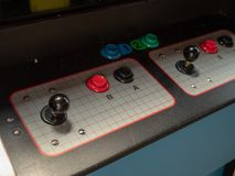 Joystick and button controls of classic arcade cabinet in dark arcade royalty free stock photo