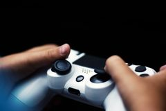 Joystick in game isolated in black. Close-up of hands holding gamepad in black background. stock photos