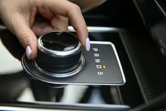 Women`s hand includes a drive mode on the automatic transmission close-up. The joystick gear shift of the automatic transmission. women`s hand includes a drive royalty free stock images
