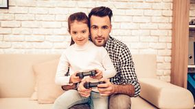Joystick in Hand. Father and Daughter. Spend Time Together. Father`s day. Man Playing with Girl. Video Game. White Interior. Sitting on Sofa. Girl with royalty free stock photography