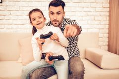 Joystick in Hand. Father and Daughter. Spend Time Together. Father`s day. Man Playing with Girl. Video Game. White Interior. Sitting on Sofa. Girl with stock photo