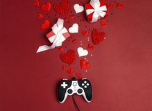 Joystick with romantic decorations on red background. Holidays gaming concept. St. Valentines Day concept. Flat lay, top view royalty free stock images