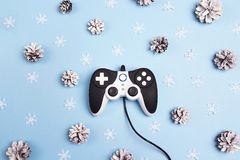 Joystick with winter holidays decorations on blue background. Holidays gaming concept royalty free stock photography