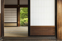 Traditional japanese room interior with open doors and garden. View into a traditional japanese room with open shoji, tatami and glimpse on the garden behind the Stock Photo