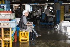Fisherman reading newspaper at the Tsukiji fish market in Tokyo Japan Stock Photos