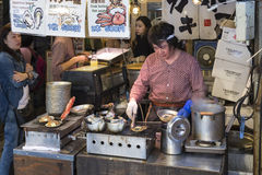 Cook preparing fresh clams at the Tsukiji fish market in Tokyo Japan. The outer market at the tsukiji fish market in Tokyo, Japan. Tradesmen prepare fresh Stock Photography