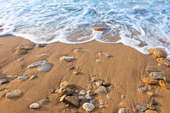 Wave of the ocean on the beach  with sand and stones Stock Photo