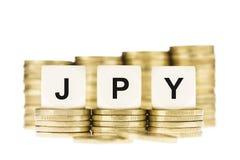 JPY (japansk valuta) över bunten för guld- mynt som isoleras på vit Arkivfoto