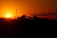 Järnmalmbearbetningsanläggning på solnedgången Arkivfoto