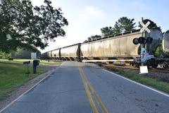 Järnvägbilar på korsningen Arkivbild