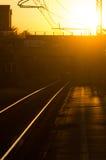 Järnvägen spårar på solnedgången Arkivbilder