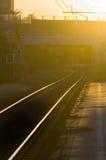 Järnvägen spårar på solnedgången Arkivbild