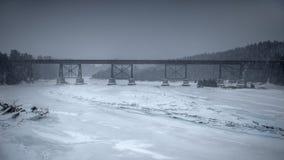 Järnvägsbro över den djupfrysta floden Arkivfoto