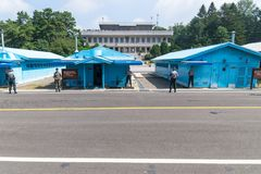 JSA within DMZ, Korea - September 8 2017: 5 UN soldiers and one normal soldier in front of blue buildings at North South Korean bo Royalty Free Stock Photography
