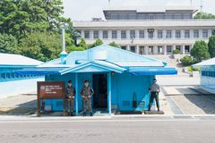 JSA inom DMZ, Korea - September 8 2017: FN tjäna som soldat och tjäna som soldat i camoulagekläder framme av blåa byggnader på no Arkivbild