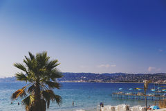 Juan Les Pins beach, Mediterranean tourist destination on the Fr. JUAN LES PINS, FRANCE - September 20th, 2016: Blue Mediterranean landscape and French beach Royalty Free Stock Photography