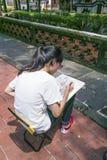 juan Lin ogródu i dworu Rodzinny celowniczy widok, jeden dziewczyna siedzi na krześle i rysuje drzewa na papierze z ołówkiem Obraz Royalty Free