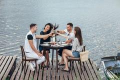 Jubel! Grupp av vänner som tycker om den utomhus- picknicken i flodpir arkivbild