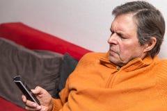 Jubilado en un sofá con el teléfono Imagen de archivo libre de regalías
