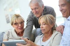 Jubilados alegres que ríen y que usan la tableta imagen de archivo