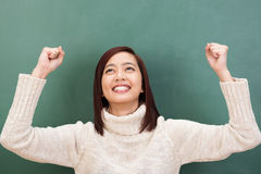 Jubilant Asian student cheering in elation. Jubilant attractive young Asian student cheering in elation raising her fists in the air in her excitement against a Stock Image