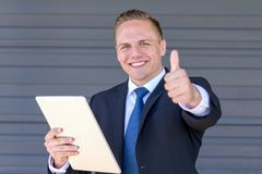 Jubilant businessman giving a thumbs up. Jubilant young businessman holding a tablet in his hand giving a thumbs up gesture of success with a satisfied smile Stock Photography