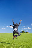 Jubilant businessman jumping for joy. With his arms raised and back to the camera in a lush green field Stock Image