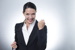 Jubilant businesswoman cheering. Beautiful jubilant young businesswoman cheering with a beaming enthusiastic smile on her face as she celebrates a success, with Stock Images