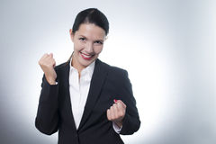 Jubilant businesswoman cheering. Beautiful jubilant young businesswoman cheering with a beaming enthusiastic smile on her face as she celebrates a success, with Stock Photography
