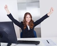 Jubilant businesswoman in office. Jubilant businesswoman raises her arms above her head in celebration of her success sitting in her office Stock Image
