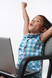 Jubilant child. Happy child with a laptop raising both hands Stock Photo