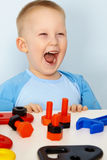 Jubilant children with toys. Jubilant children at the table with toys royalty free stock images