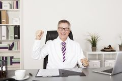 Jubilant doctor sitting cheering in his office. Jubilant middle-aged male doctor sitting cheering in his office punching the air with his fist as he celebrates a Royalty Free Stock Photos
