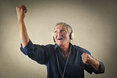 Jubilant elderly man. Listening to music through headphones Stock Photos