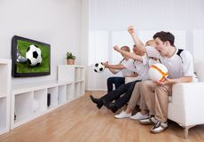 Jubilant family watching television. As they cheer on their home side in a sporting competition Royalty Free Stock Image