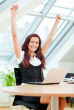 Jubilant female clerk. With laptop sitting in office Stock Image
