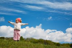 Jubilant girl. A small girl is jubilant with raised poor on a meadow before a blue easily cloudy sky Stock Photos